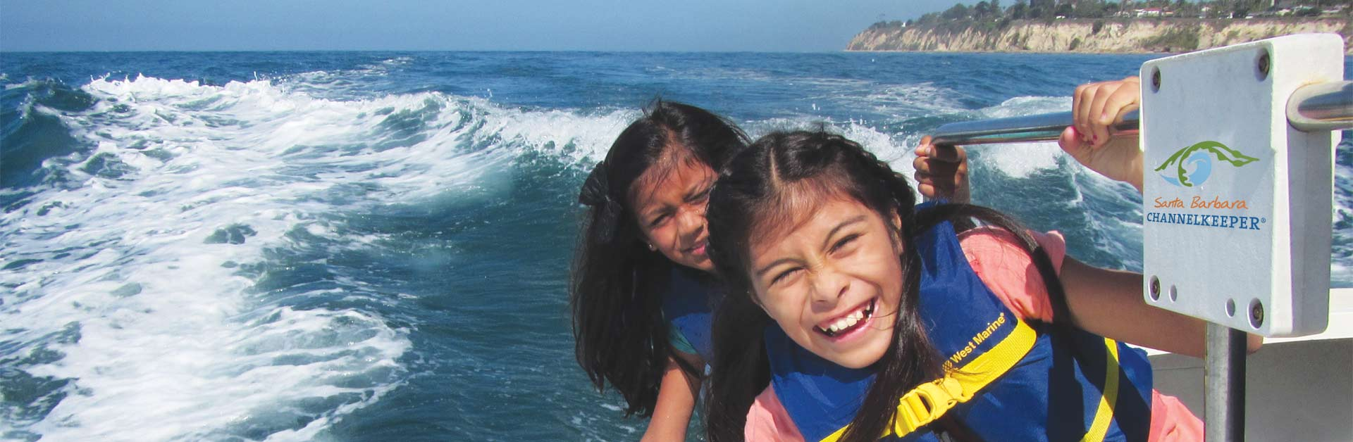 Happy kids smiling while their hands touch the water as they ride on a boat in the ocean.