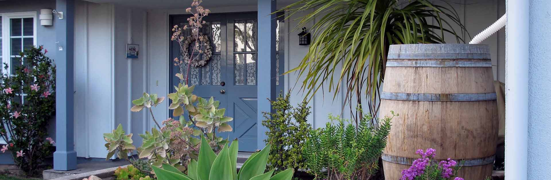 A front yard of a nice home with a rain barrel used for water conservation.