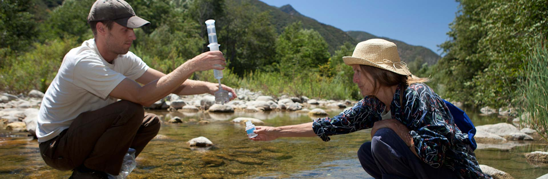 Two Santa Barbara Channelkeeper team members collecting water samples in the Ventura River.