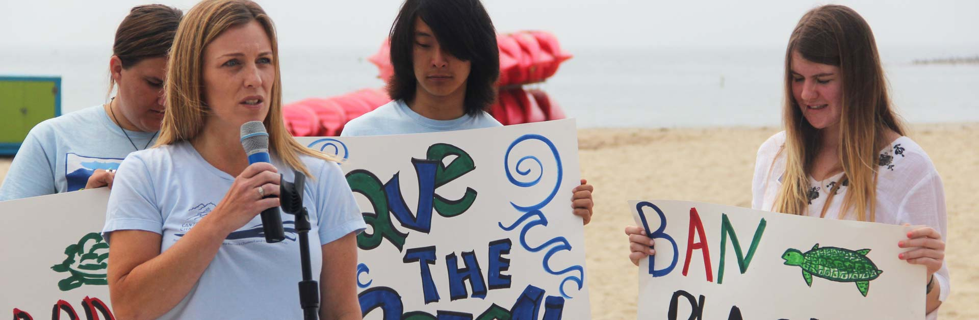 Kids holding Save the Ocean signs at a ban plastic bags rally.