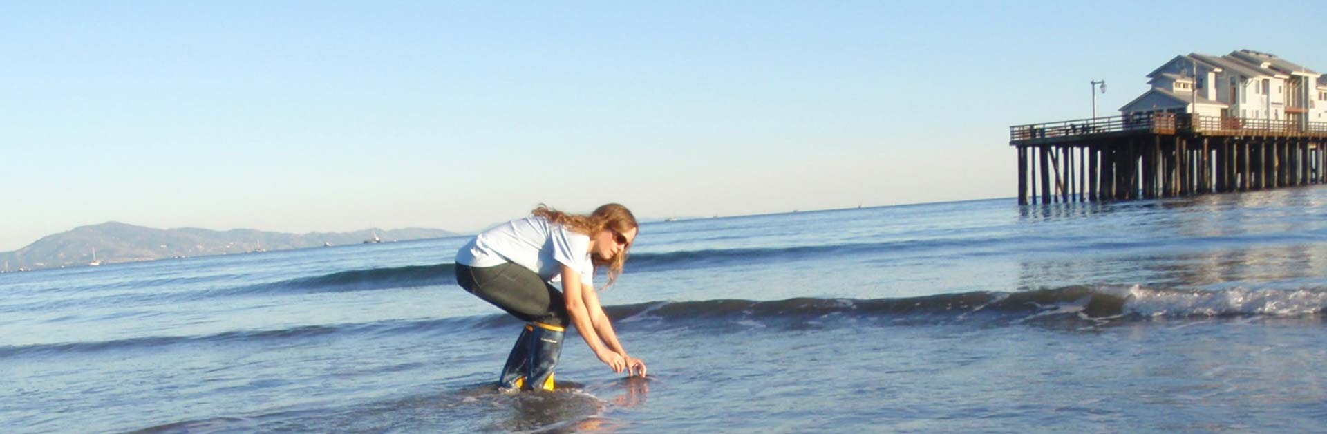 Santa Barbara Channelkeeper team member collecting water samples in the surf at a local beach for testing.