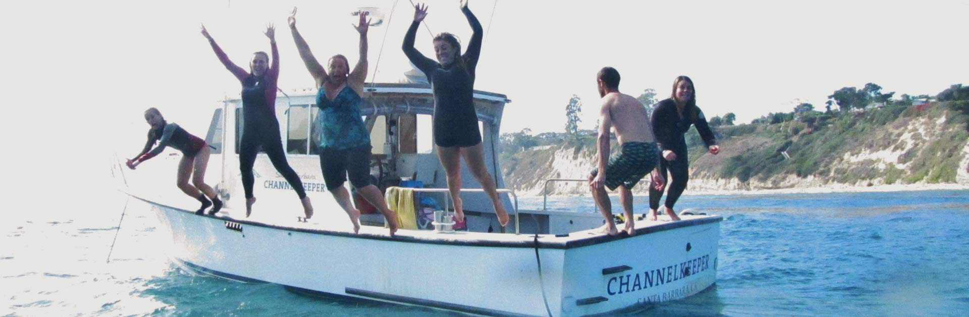 A happy group of Santa Barbara Channelkeeper members jumping off the R/V Channelkeeper boat.
